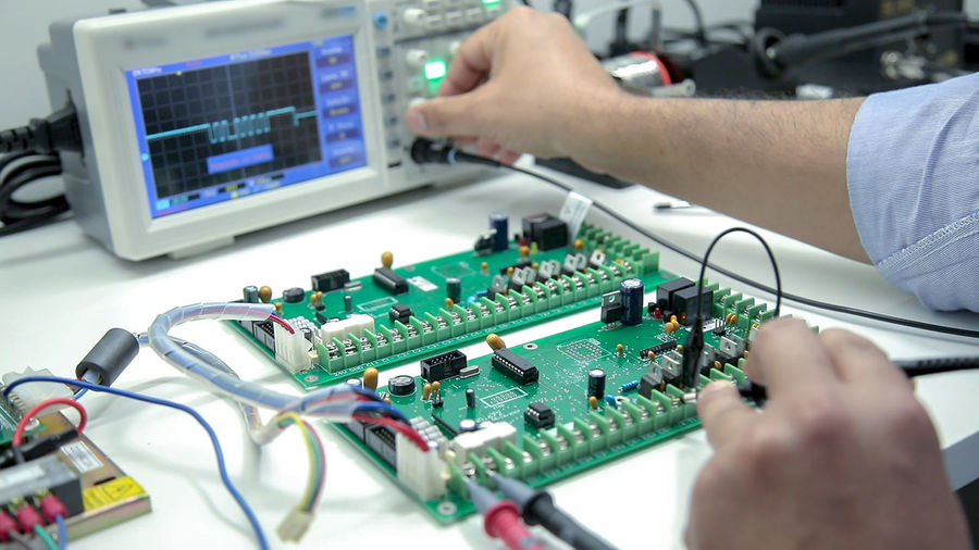 Cropped hands of worker examining mother board