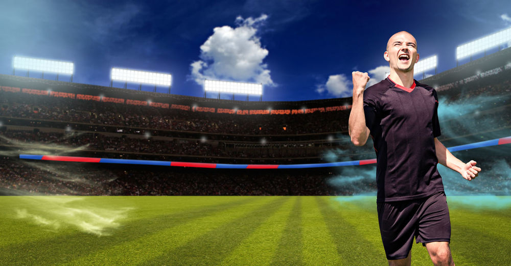 Happy man clenching fist on soccer field