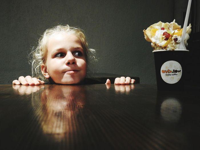 Cute girl looking at sweet food in darkroom