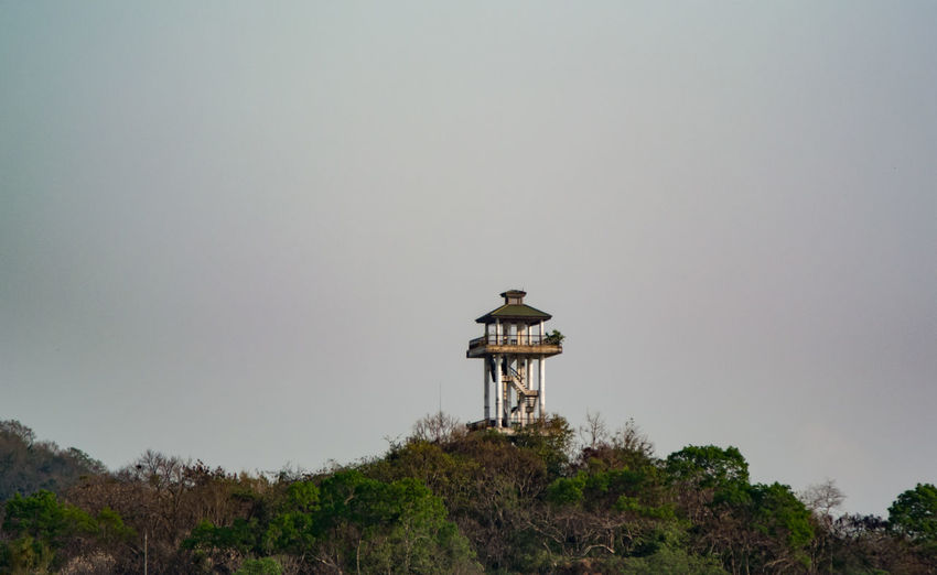 Lookout tower amidst trees against clear sky