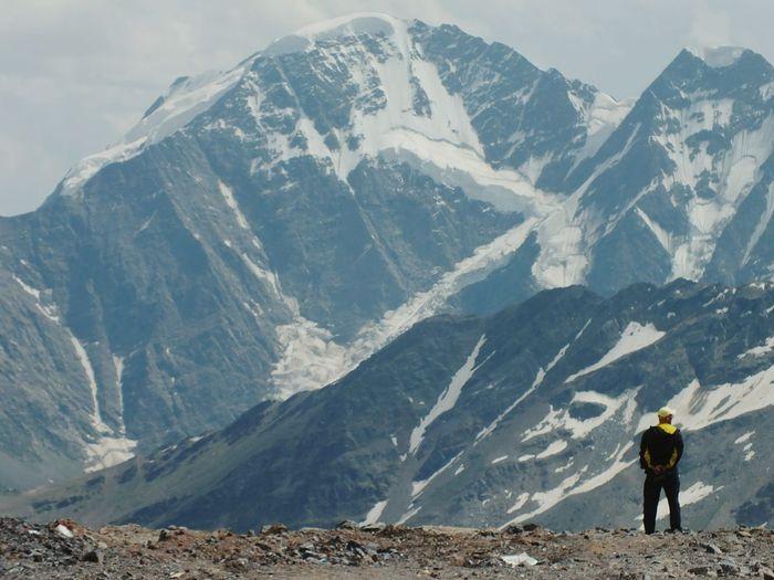 Tourist walking on snow covered mountain