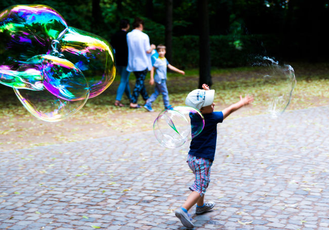 a boy and bubbles Your Ticket To Europe Blurred Motion Boys Breaking Bubble Bubble Bubble Wand Caught In The Moment Cheerful Child Childhood Day Fragility Fun Happiness Leisure Activity Mid-air Motion Outdoors Park Playing Rainbow Rupture Soap Sud Spectrum EyeEm Best Shots