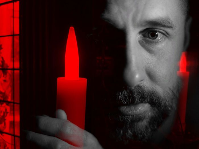Close-up portrait of man holding red light
