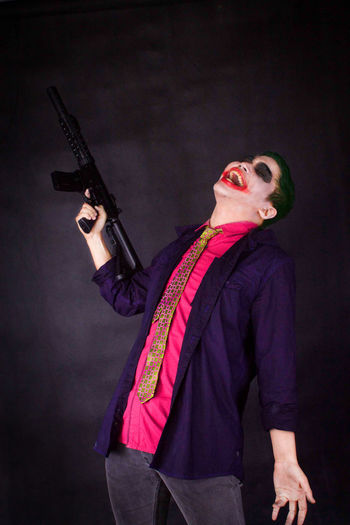 Smiling Young Man With Gun Wearing Costume Against Black Background
