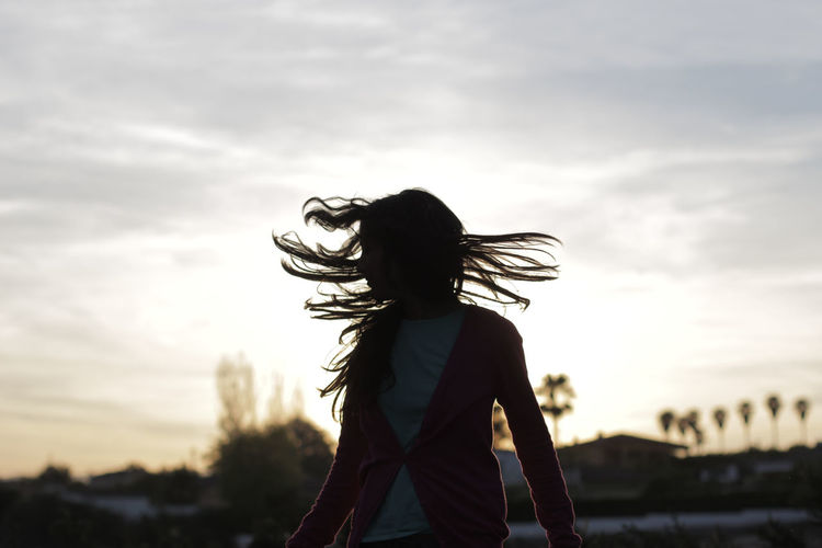 Woman with tousled hair standing against cloudy sky during sunset
