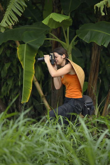 Woman photographing in grass