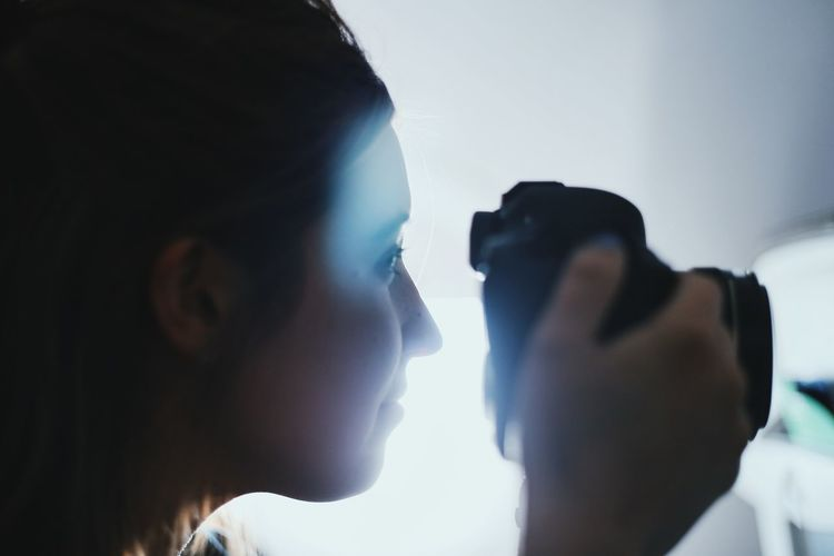 Close-Up Of Woman Photographing From Camera While Traveling In Airplane
