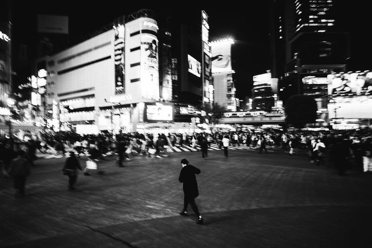 Woman standing in illuminated city at night