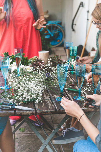 Real People Holding Group Of People Lifestyles Women Table Hand Adult Leisure Activity Human Hand Glass Celebration People Men Togetherness Midsection Human Body Part Indoors  Flower Wreath