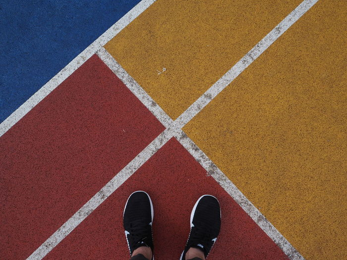 Low section of person standing on sports track
