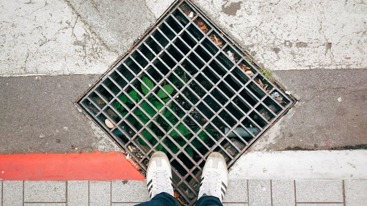 low section, human leg, sewer, manhole, metal, personal perspective, shoe, sewage, real people, high angle view, metal grate, human body part, day, one person, gutter, outdoors, directly above, standing, adult, people