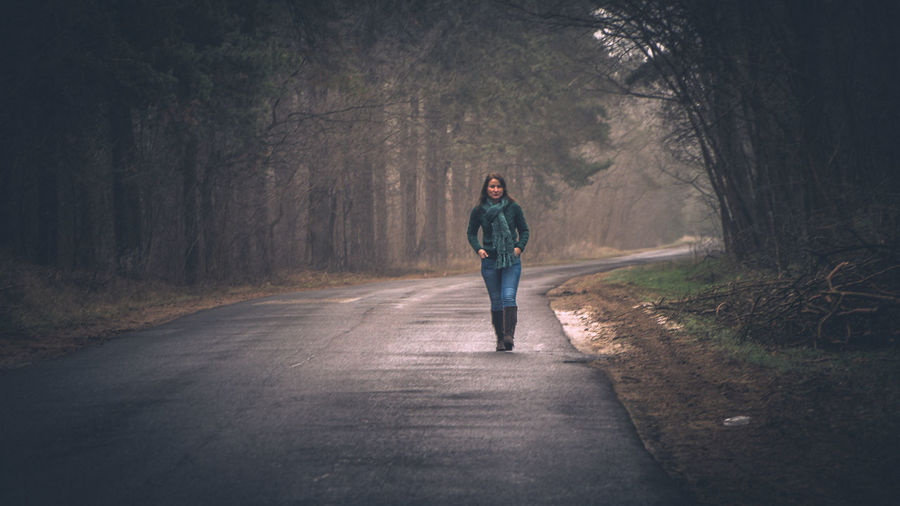 Full length of man walking on road in forest