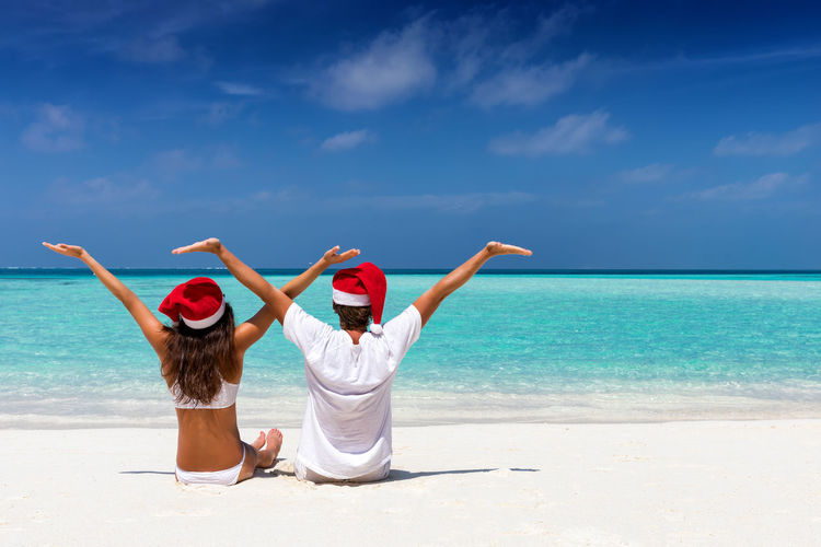 Happy couple with Christmas hats on a tropical beach Christmas Couple Hat Holiday Love Maldives Man Tropics Winter Woman Xmas Beach Caribbean Day Honeymoon Nature Outdoors Sand Sea Sky Togetherness Tropical Two People Vacations Water