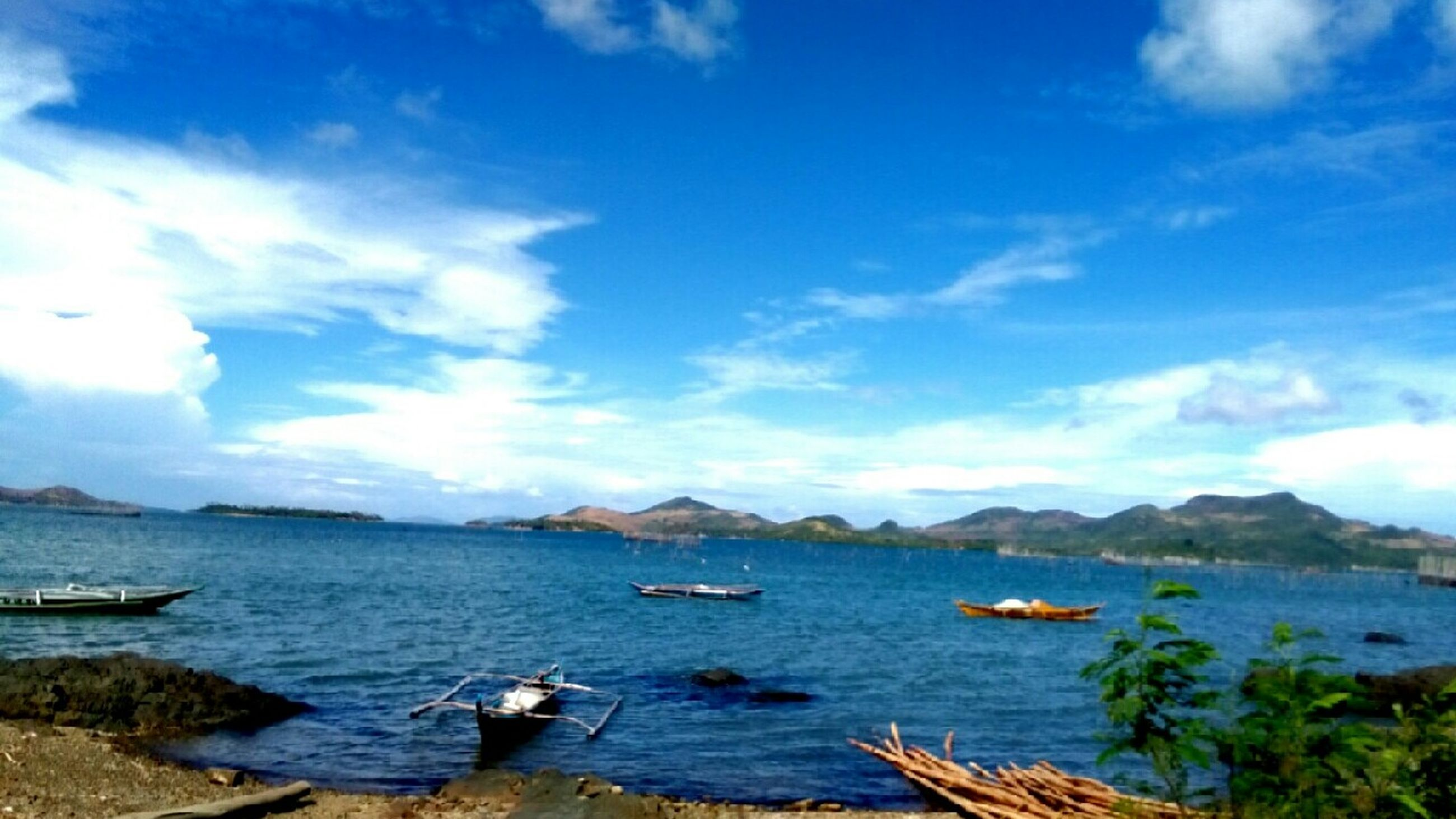 water, sky, tranquil scene, mountain, tranquility, nautical vessel, scenics, blue, beauty in nature, cloud - sky, sea, boat, nature, cloud, transportation, lake, mountain range, mode of transport, idyllic, day