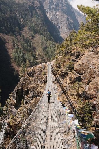 Rear view of man walking on footbridge against mountain