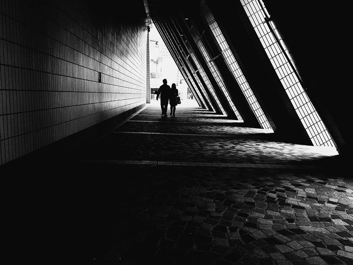 Silhouette couple walking on covered walkway