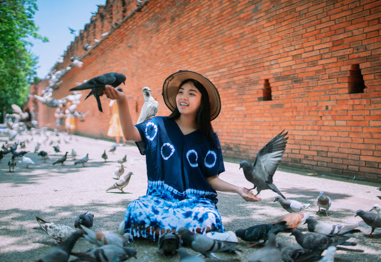 Young woman playing with pigeons