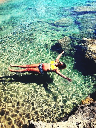 High angle view of smiling young woman swimming in sea