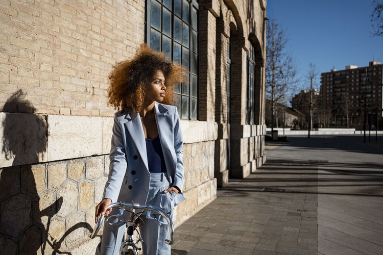 Woman looking at bicycle in city