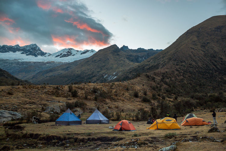 Tents on mountain against sky during sunset