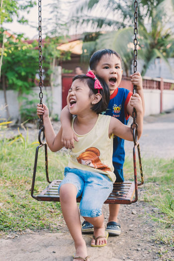 Full length of happy girl playing on swing at playground