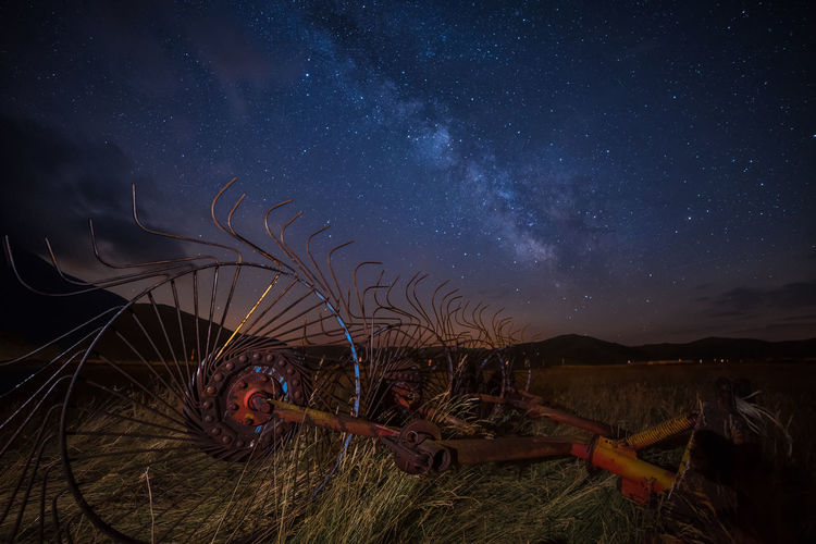 Abandoned Machinery On Grassy Field Against Star Field At Night