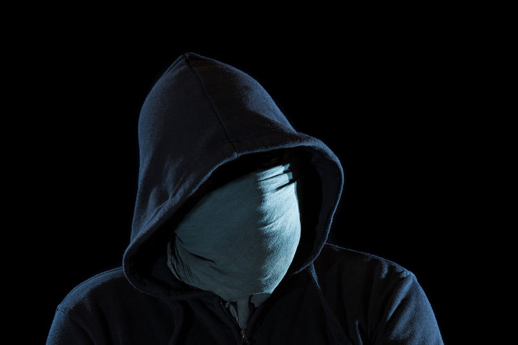Portrait of person wearing mask against black background