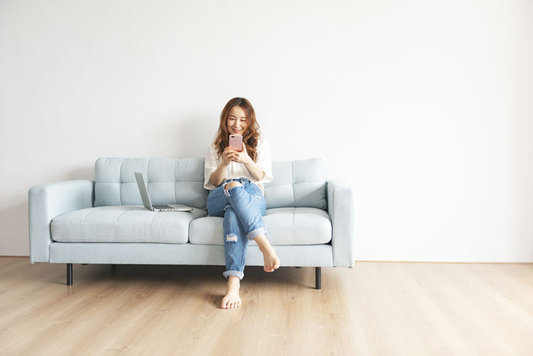 Smiling Beautiful Woman Using Mobile Phone While Sitting On Sofa At Home
