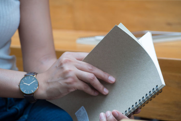 Midsection of woman holding book by table