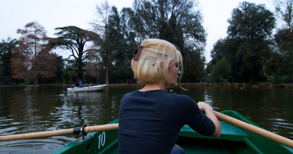Rear view of woman in rowing boat on lake