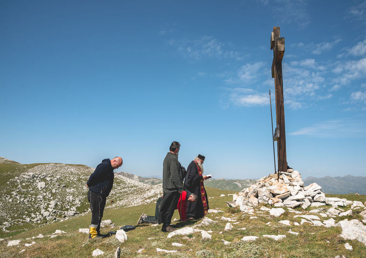 People by cross on mountain