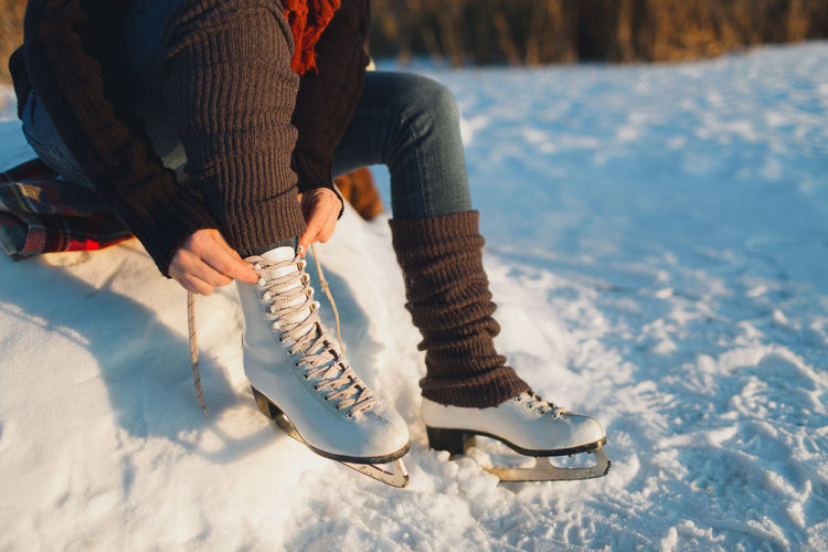Low section of woman wearing ice skates on frozen lake