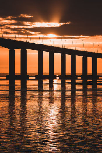 Architectural Column Architecture Beauty In Nature Bridge Bridge - Man Made Structure Built Structure Cloud - Sky Connection Nature No People Orange Color Outdoors Reflection Scenics - Nature Sea Silhouette Sky Sun Sunrise Water Waterfront