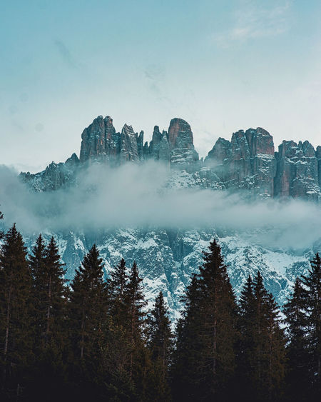 Scenic view of pine trees against dolomites and sky during winter