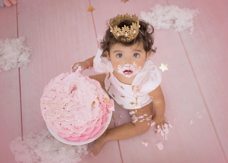 Cute baby girl with birthday cake sitting at home