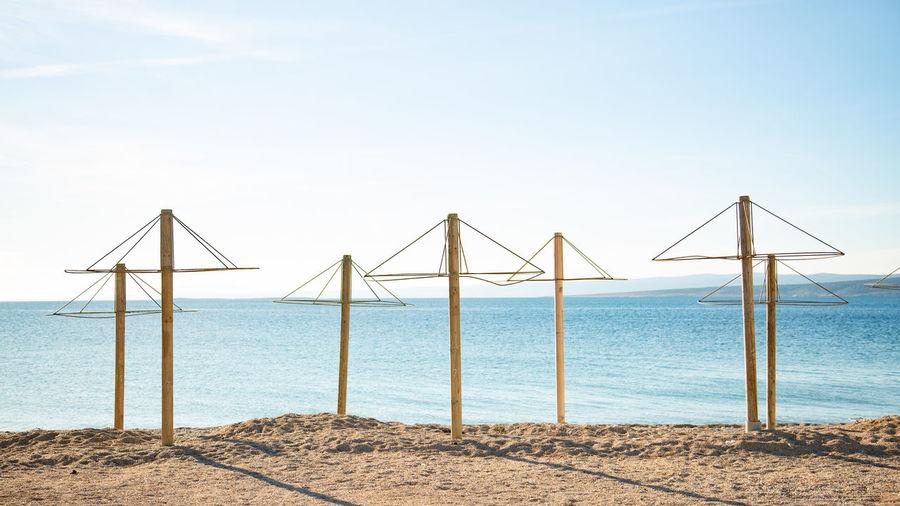 Wind turbines on beach against clear sky