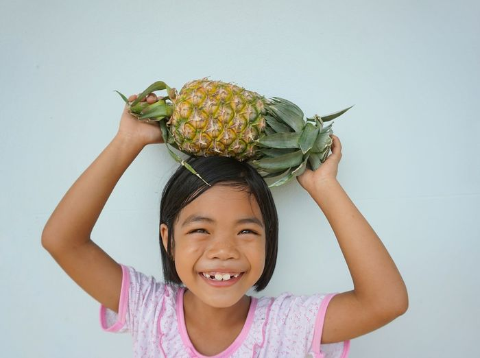 Portrait of smiling girl holding fruit