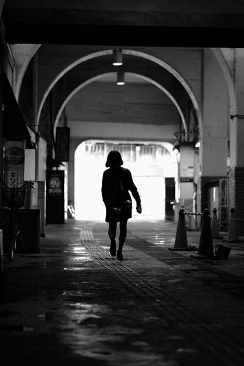 Silhouette of woman walking at station