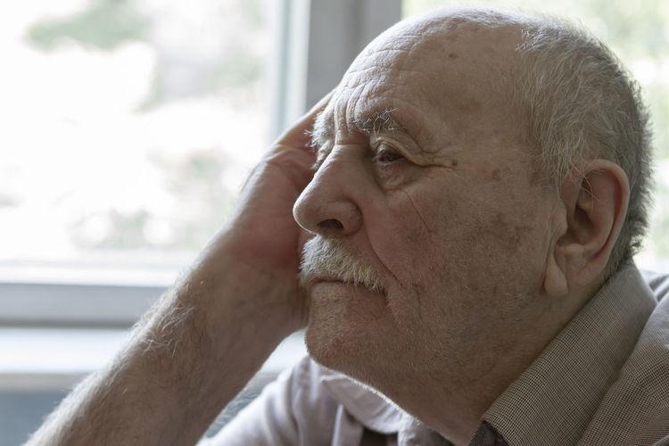 Close-Up Of Senior Man Looking Away Sitting At Home