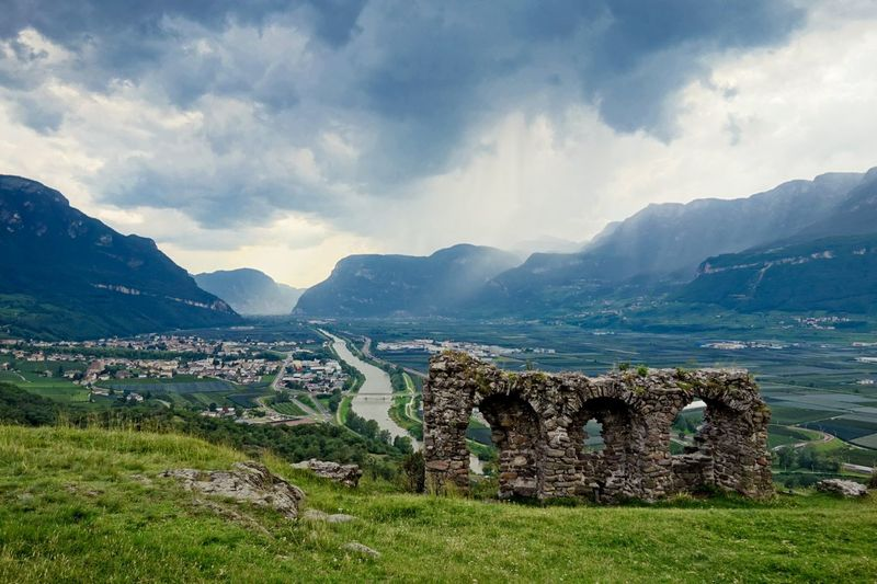 Old ruins on mountain against cloudy sky