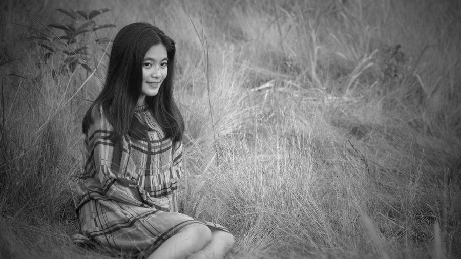 Smiling young woman looking away while sitting on dry grass