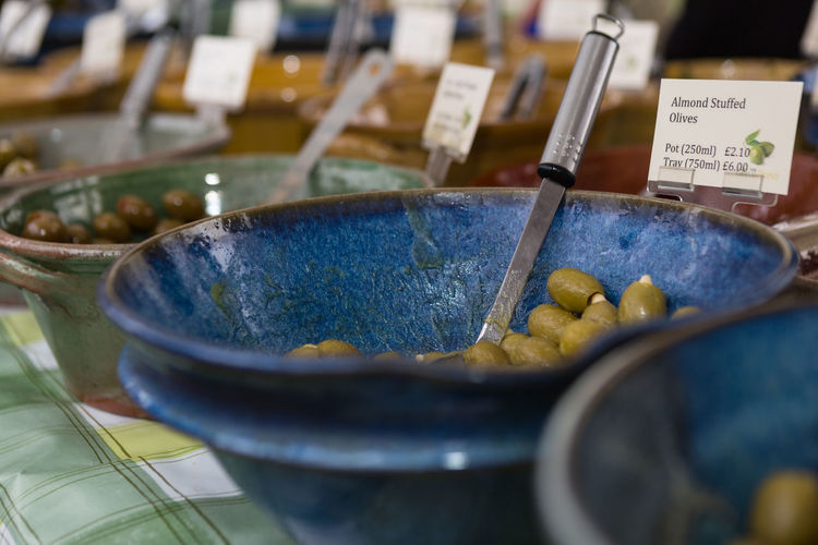 Close-up of olives in containers with labels at market stall