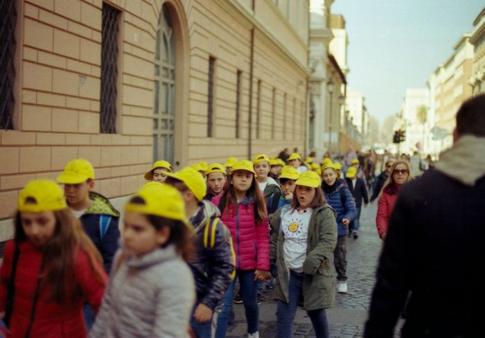 Kids going to school Analogue Photography Cap Children City Commuters Commuting Crowd Italy Kids Large Group Of People Nikon Fm2 Outdoors Queue Real People Rome School Togetherness Walking Yellow Yellow Hat