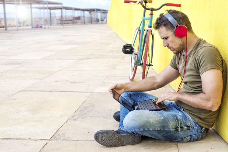 Side view of attractive guy is sitting on the floor with trendy look, writing in notebook using computer, having headphones while looking at screen against a yellow wall One Person Casual Clothing Real People Young Men Sitting Young Adult Full Length Side View Holding Men Leisure Activity Crouching Lifestyles Day Flooring Cross-legged Focus On Foreground Jeans Young Man Hipster Trendy Fashionable Hat T-shirt Sitting Outdoors Headphones Bike Fixie Laptop Using Laptop Vintage Yellow