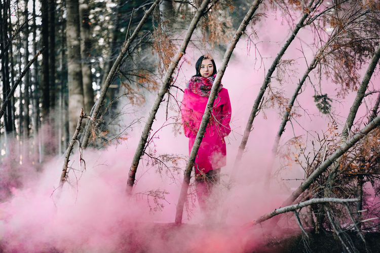 Pink Pink Smoke Nature Forest One Person One Woman Only Women Smoke Smoke - Physical Structure Smoke Bomb People Looking At Camera Warm Clothing Tree Full Length Young Women Spraying Pink Color Sky Branch Bare Tree Woods Posing Tree Trunk 2018 In One Photograph