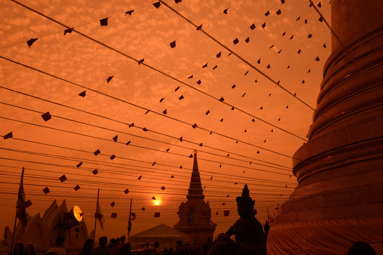 Low Angle View Of Decorations At Temple Against Orange Sky During Sunset