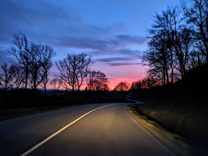 Road by silhouette trees against sky at sunset