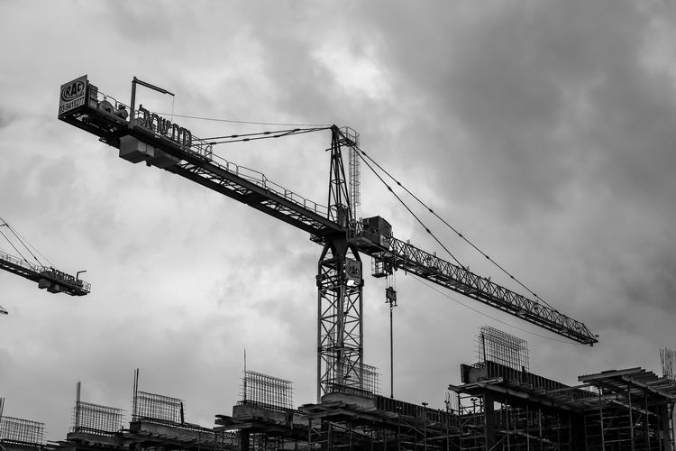 Low angle view of cranes at construction site against sky
