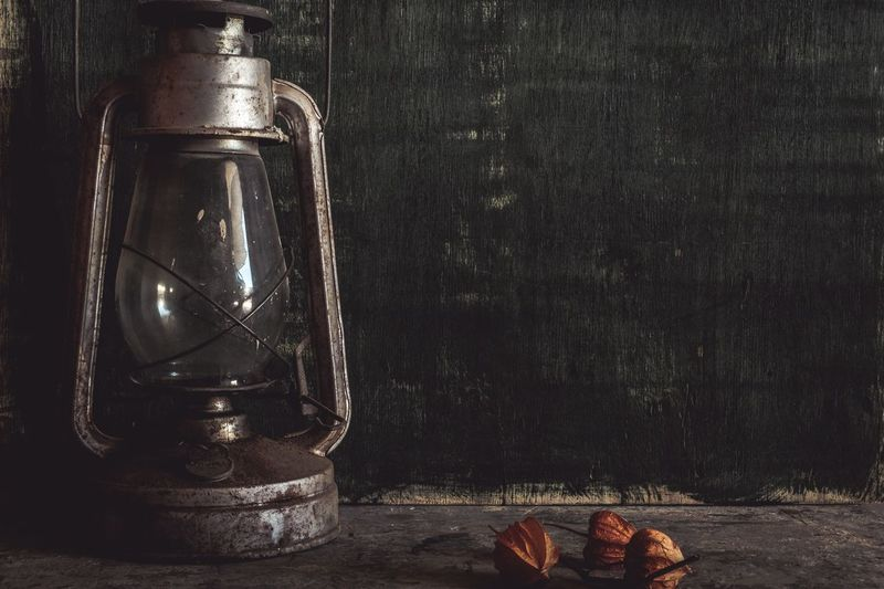 Winter cherries and oil lamp on table