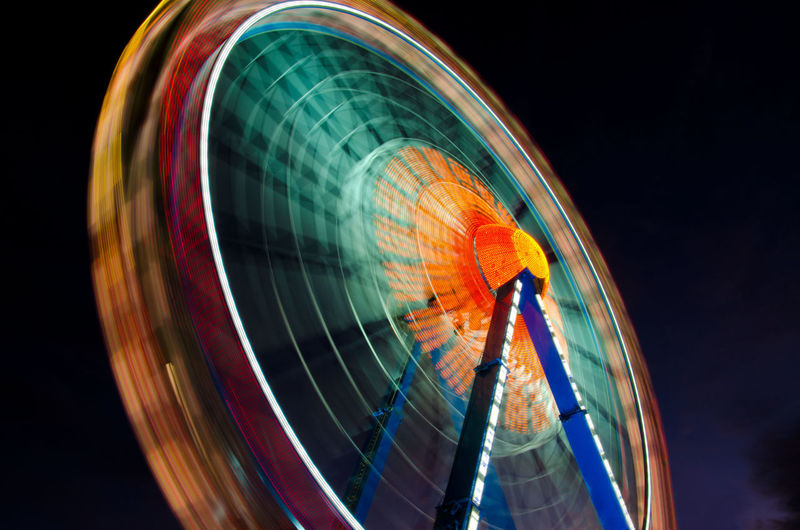 Blurred motion of ferris wheel against sky at night
